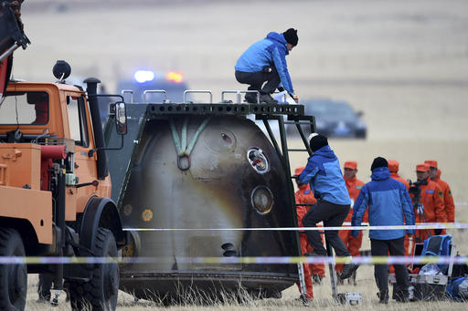 In this photo released by Xinhua News Agency, ground crew check on the re-entry capsule of Shenzhou 11 spacecraft after it landed in north China's Inner Mongolia Autonomous Region, Friday, Nov. 18, 2016. A pair of Chinese astronauts returned Friday from a monthlong stay aboard the country's space station, China's sixth and longest crewed mission and a sign of the growing ambitions of its rapidly advancing space program. (Ren Junchuan/Xinhua via AP)