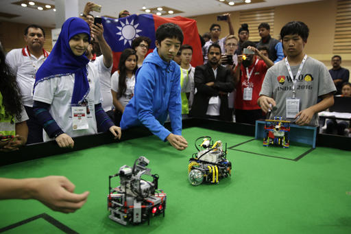 In this Sunday, Nov. 27, 2016, photo, participants from Taiwan watch their robots playing a soccer match during the World Robot Olympiad in New Delhi, India. The weekend games brought more than 450 teams of students from 50 countries to the Indian capital. (AP Photo/Tsering Topgyal)