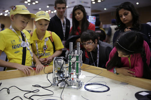 In this Sunday, Nov. 27, 2016 photo, participants and spectators look at a 3D printer made of LEGO parts during the World Robot Olympiad in New Delhi, India. The weekend games brought more than 450 teams of students from 50 countries to the Indian capital. (AP Photo/Tsering Topgyal)