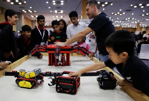 In this Sunday, Nov. 27, 2016, photo, a boy plays with a robot during the World Robot Olympiad in New Delhi, India. The weekend games brought more than 450 teams of students from 50 countries to the Indian capital. (AP Photo/Tsering Topgyal)