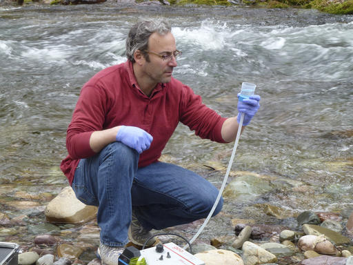 This April 17, 2014 photo provided by the U.S. Forest Service shows Michael K. Schwartz in the process of filtering 5 liters of water to concentrate DNA on a filter to be analyzed at the National Genomics Center for Wildlife and Fish Conservation, on Rattlesnake Creek near Missoula, Mont. Scientists are aiming to create a biodiversity map that identifies thousands of aquatic species in every river and stream in the western United States. They say that by next summer, the first Aquatic Environmental DNA Atlas will be available to the public. (Kellie Carim/U.S. Forest Service via AP)