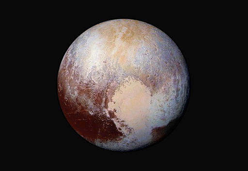 This image made available by NASA on July 24, 2015 shows a combination of images captured by the New Horizons spacecraft with enhanced colors to show differences in the composition and texture of Pluto's surface. The deep icy basin in Pluto's heart-shaped region may be a natural sinkhole. In a study published Wednesday, Nov. 30, 2016, a team led by University of Maryland astronomer Douglas Hamilton suggests the basin may have resulted from the weight of surface ice. (NASA/JHUAPL/SwRI via AP)