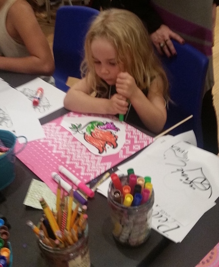 Young girl hard at work on her peace flag at Laguna Art Museum