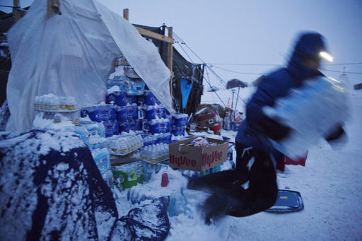 Ray Franks, of New York, trips while carrying a case of water from a storage supply at the Oceti Sakowin camp where people have gathered to protest the Dakota Access oil pipeline in Cannon Ball, N.D., Tuesday, Dec. 6, 2016. Many Dakota Access oil pipeline opponents who've gathered for months in the camp are committed to staying despite wintry weather and demands that they leave. An overnight storm brought several inches of snow, winds gusting to 50 mph and temperatures that felt as cold as 10 degrees below zero. (AP Photo/David Goldman)