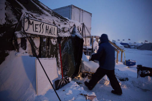 Ray Franks, of New York, carries a case of water into a mess hall at the Oceti Sakowin camp where people have gathered to protest the Dakota Access oil pipeline in Cannon Ball, N.D., Tuesday, Dec. 6, 2016. An overnight storm brought several inches of snow, winds gusting to 50 mph and temperatures that felt as cold as 10 degrees below zero. (AP Photo/David Goldman)