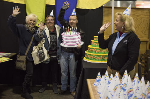 Michele Frymen, from left, Christy Anderson and Jacob Anderson, all from Columbus, hold up a birthday cake and wave as they get their picture taken during some festivities in the food court as part of the 60th birthday celebration for Colo, the nation's oldest living gorilla, at the Columbus Zoo and Aquarium, Thursday, Dec. 22, 2016 in Columbus, Ohio. Colo was the first gorilla in the world born in a zoo and has surpassed the usual life expectancy of captive gorillas by two decades. Her longevity is putting a spotlight on the medical care, nutrition and up-to-date therapeutic techniques that are helping lengthen zoo animals' lives. (AP Photo/Ty Wright)