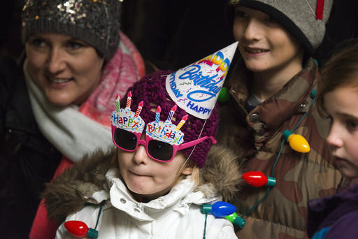 Stella Luken, 5 of Dublin, Ohio, wears a birthday hat and a pair of birthday sun glasses as she waits in line to see Colo, the nation's oldest living gorilla, during Colo's 60th birthday party at the Columbus Zoo and Aquarium, Thursday, Dec. 22, 2016 in Columbus, Ohio. Colo was the first gorilla in the world born in a zoo and has surpassed the usual life expectancy of captive gorillas by two decades. Her longevity is putting a spotlight on the medical care, nutrition and up-to-date therapeutic techniques that are helping lengthen zoo animals' lives. (AP Photo/Ty Wright)