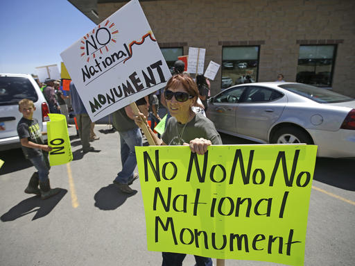 This July 14, 2016, file photo, a protester holds her signs after U.S. Interior Secretary Sally Jewell arrived for a meeting with San Juan County Commissioners in Monticello, Utah. President Barack Obama designated two national monuments Wednesday, Dec. 28, at sites in Utah and Nevada that have become key flashpoints over use of public land in the U.S. West. The White House says Bears Ears National Monument in Utah will cover 1.35 million acres of tribal land in the Four Corners region. (AP Photo/Rick Bowmer, File)