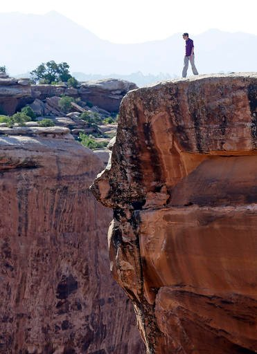 This July 14, 2016, file photo, U.S. Interior Secretary Sally Jewell looks in to a canyon at Gemini Bridges near Moab, Utah, during a tour to meet with proponents and opponents to the