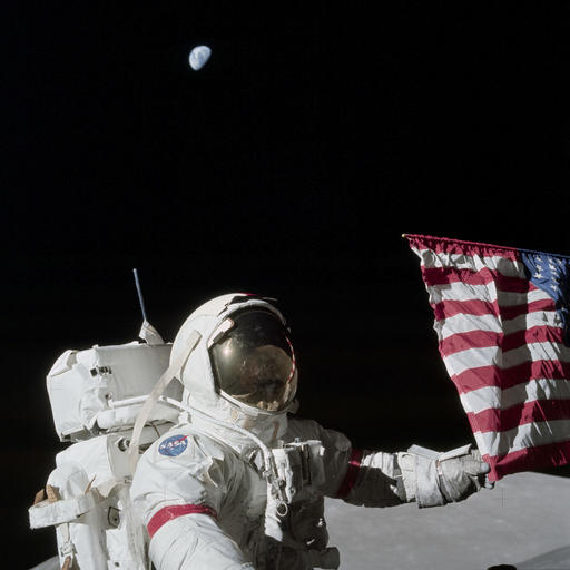 n this Dec. 12, 1972, photo provided by NASA, Apollo 17 commander Eugene Cernan holds the lower corner of an American flag during the mission's first Extravehicular activity on the moon. NASA announced that former astronaut Cernan, the last man to walk on the moon, died Monday, Jan. 16, 2017, surrounded by his family. He was 82. (Harrison J.