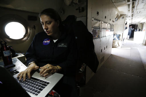 In this Feb. 17, 2017 photo, NASA's lead aircraft integration engineer Eugenia De Marco works inside the Navy P-3 Orion aircraft used for a NASA-led experiment called SnowEx, at Peterson Air Force Base in Colorado Springs, Colo. Instrument-laden aircraft are surveying the Colorado high country this month as scientists search for better ways to measure how much water is locked up in the world's mountain snows - water that sustains a substantial share of the global population. (AP Photo/Brennan Linsley)