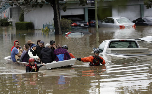 Rescue crews take out residents from a flooded neighborhood Tuesday, Feb. 21, 2017, in San Jose, Calif. Rescuers chest-deep in water steered boats carrying dozens of people, some with babies and pets, from a San Jose neighborhood inundated by water from an overflowing creek Tuesday. (AP Photo/Marcio Jose Sanchez)