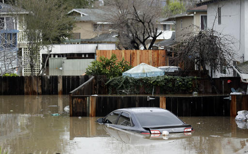 Cars and backyards are flooded in a neighborhood Tuesday, Feb. 21, 2017, in San Jose, Calif. Rescuers chest-deep in water steered boats carrying dozens of people, some with babies and pets, from a San Jose neighborhood inundated by water from an overflowing creek Tuesday. (AP Photo/Marcio Jose Sanchez)