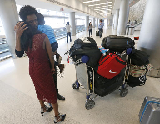 Olympic silver medalist Feyisa Lilesa, of Ethiopia, hugs his wife Iftu Mulia, and his son Sora, 3, while picking up his family at Miami International Airport, Tuesday, Feb. 14, 2017, in Miami. Lilesa arrived in the U.S. on a special skills visa, which allows him to train and compete until January. His wife, son, daughter and brother joined him in Miami Tuesday. (AP Photo/Wilfredo Lee)