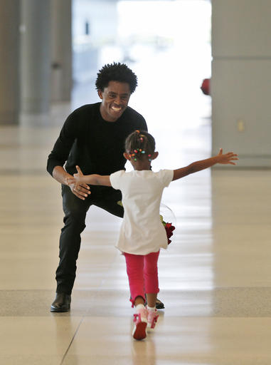 Olympic silver medalist Feyisa Lilesa, left, of Ethiopia, crouches to hug his daughter Soko, 5, while picking up his family at Miami International Airport, Tuesday, Feb. 14, 2017, in Miami. Lilesa arrived in the U.S. on a special skills visa, which allows him to train and compete until January. His wife, son, daughter and brother joined him in Miami Tuesday. (AP Photo/Wilfredo Lee)
