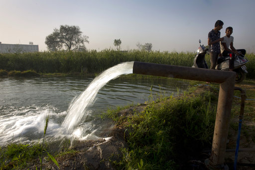 Indians sit on a two-wheeler and talk as water from a bore well irrigates their field on the World Water Day on the outskirts of New Delhi, India, Wednesday, March 22, 2017. India has the world's highest number of people without access to clean water. UNICEF says nearly 78 million Indians - about 5 percent of the country's 1.3 billion population - must make do with contaminated water sources or buy water at high rates. (AP Photo/Manish Swarup)