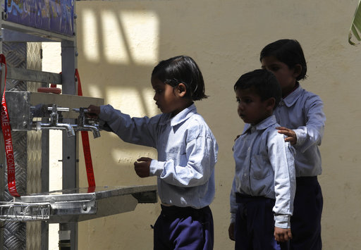 Schoolchildren line up to drink water from a newly set up water filtration tower at their school in Nai Basti Village, some 55 kilometers (35 miles) from in New Delhi, India, Wednesday, March 22, 2017. Schoolchildren cheered and village women clapped as a gush of clean water flowed through a set of gleaming steel taps connected to a newly installed water filtration plant in a dusty north Indian village on Wednesday. (AP Photo/Manish Swarup)