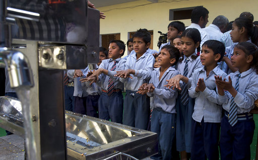 Schoolchildren learn to wash their hands before drinking water from newly set up water filtration tower in their school in Nai Basti Village, some 55 kilometers (35 miles) from in New Delhi, India, Wednesday, March 22, 2017. Schoolchildren cheered and village women clapped as a gush of clean water flowed through a set of gleaming steel taps connected to a newly installed water filtration plant in a dusty north Indian village on Wednesday. (AP Photo/Manish Swarup)