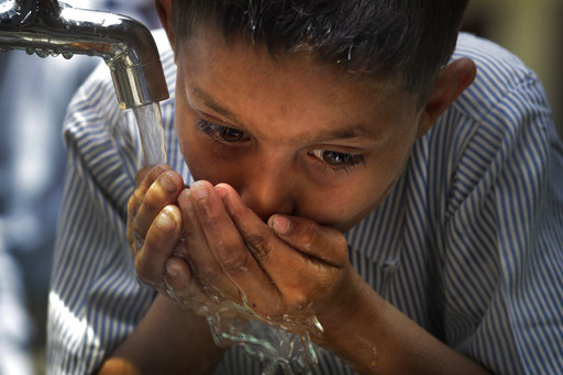 A boy drinks water from a newly set up water filtration tower in his school provided by Planet Water foundation, a non-governmental organization based in U.S. in Nai Basti Village, some 55 kilometers (35 miles) from in New Delhi, India, Wednesday, March 22, 2017. Schoolchildren cheered and village women clapped as a gush of clean water flowed through a set of gleaming steel taps connected to a newly installed water filtration plant in a dusty north Indian village on Wednesday. (AP Photo/Manish Swarup)