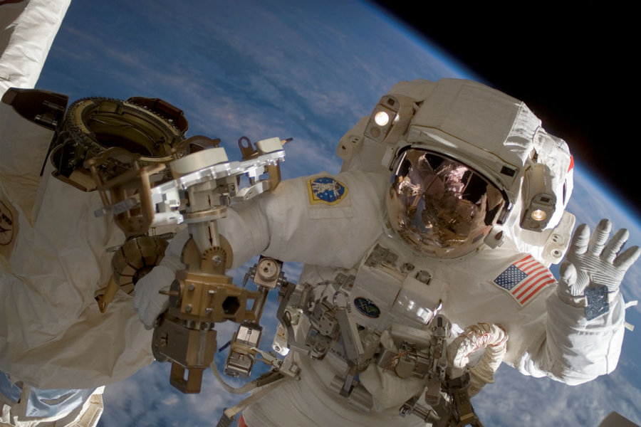 Astronaut Clay Anderson waves during a spacewalk outside the International Space Station. Astronauts traveling to and from Mars would be bombarded with as much cosmic radiation as they'd get from a full-body CT scan about once a week for a year, researchers reported in 2013. (NASA/AP photo)