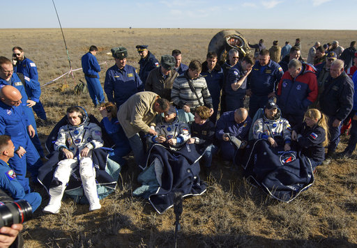 NASA astronaut Shane Kimbrough, left, Russian cosmonaut Sergey Ryzhikov of Roscosmos, center, and Russian cosmonaut Andrey Borisenko of Roscosmos sit in chairs outside the Soyuz MS-02 spacecraft a few moments after they landed in a remote area near Dzhezkazgan, Kazakhstan on Monday, April 10, 2017. Kimbrough, Ryzhikov, and Borisenko returned from the International Space Station. (Bill Ingalls/NASA via AP)