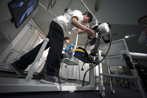 A medical assistant helps to attach a model to demonstrate the Welwalk WW-1000, a wearable robotic leg brace designed to help partially paralyzed people walk at the main system with treadmill and monitor, at Toyota Motor Corp.'s head office in Tokyo, Wednesday, April 12, 2017. Toyota Motor Corp.'s Welwalk WW-1000 system is made up of a motorized mechanical frame that fits on a person's leg from the knee down.(AP Photo/Eugene Hoshiko)