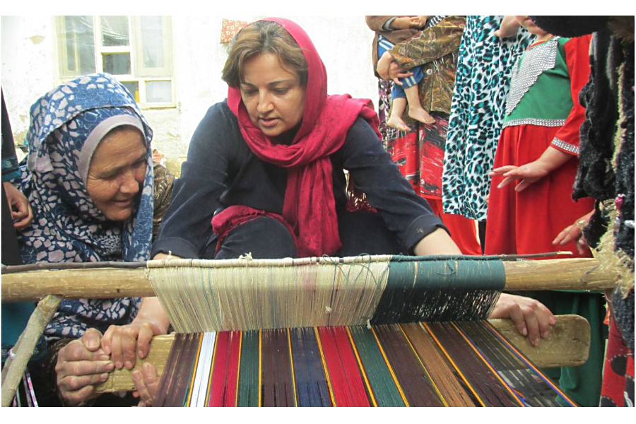 Women show Seema Ghani how to make shawls in Qizel Kent village, Afganistan, in 2015. (Courtesy of Hand in Hand Afghanistan)