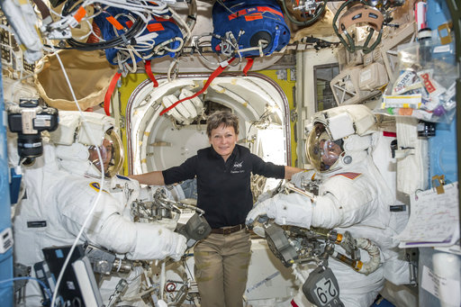 In this Jan. 13, 2017 file photo made available by NASA, astronaut Peggy Whitson, center, floats inside the Quest airlock of the International Space Station with Thomas Pesquet, left, and Shane Kimbrough before their spacewalk. Early Monday, April 24, 2017, the International Space Station commander surpassed the 534-day, two-hour-and-48-minute record set last year by Jeffrey Williams for most accumulated time in orbit by an American. Whitson already was the world's most experienced spacewoman and female spacewalker and, at age 57, the oldest woman ever in space. (NASA via AP, File)