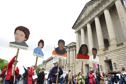People hold signs of poineering women in science in front the U.S. Environmental Protection Agency during the March for Science in Washington, Saturday, April 22, 2017. Scientists, students and research advocates rallied from the Brandenburg Gate to the Washington Monument on Earth Day, conveying a global message of scientific freedom without political interference and spending necessary to make future breakthroughs possible. (AP Photo/Sait Serkan Gurbuz)