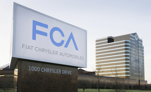 This Tuesday, May 6, 2014, file photo shows a sign outside Fiat Chrysler Automobiles world headquarters in Auburn Hills, Mich. Fiat Chrysler and Google said Tuesday, April 25, 2017, for the first time will offer rides to the public in the self-driving automobiles they are building under an expanding partnership. (AP Photo/Carlos Osorio, File)