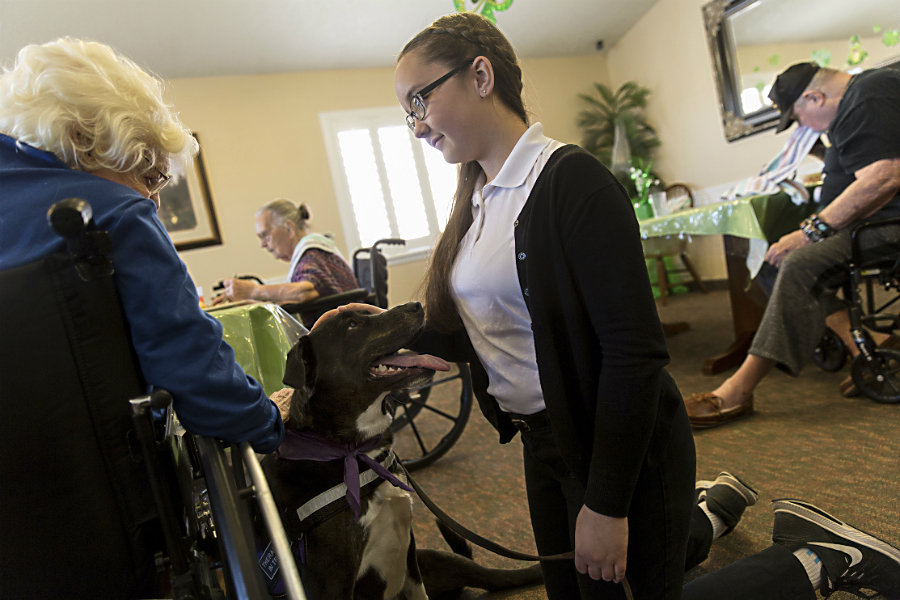 Resident Irma Porter pets Lucy as she and her owner Alexandra Burnham visit residents at the Beehive Homes in Farmington, N.M. (Jon Austria/The Daily Times/AP)
