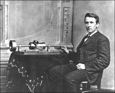 Thomas Edison sitting next to a phonograph<br> (www.hfmgv.org/exhibits/ edison/chrono.asp)
