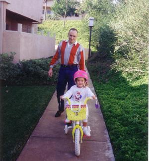 Stu teaching Caitlin how to ride her bike (Personal album)