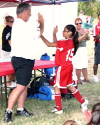 Jack Hitchens gives a high five to a U12 player. (Hannah Leake)