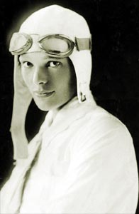 Amelia in a white aviator suit and cap in white (http://www.ameliaearhart.com/about/historicalphotos.html)