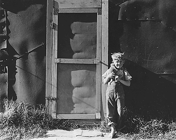"""Contra Costa County, California. Little boy from """"back East"""" in front of tar paper house in the Davis camp, where he now lives.<br>"""