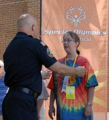 An officer awards metals to S.O. athletes.<br>(K. Crockett)