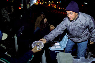 "Jorge Muñoz handing out food at ""his corner"" (NY Daily News)"
