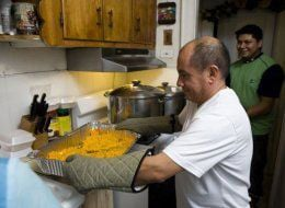 Muñoz preparing hot meals to go hand out (Huffington Post)