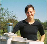 Courtney Schumacher with her group's disdrometer, an instrument that measures the drop size distribution of rain (essentially a very expensive microphone). (Image courtesy of Texas A&M University)