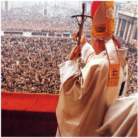 The Pope stands before thousands of people. (https://www.jesuschristsavior.net/JohnPaul.jpeg )