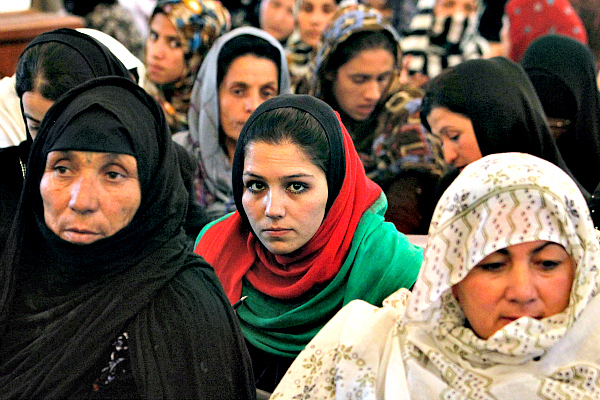 Women listen to a speech by Afghanistan's President Hamid Karzai in Kabul in May 2013. The Afghan Women's Writing Project is helping women express their thoughts and opinions through poetry. But the identity of women poets must be carefully guarded for their own safety.  <P>Omar Sobhani/Reuters/File