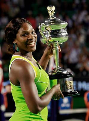 Serena Williams smiling while holding a trophy. (http://abagond.files.wordpress.com/2007/12/serena18.jpg)