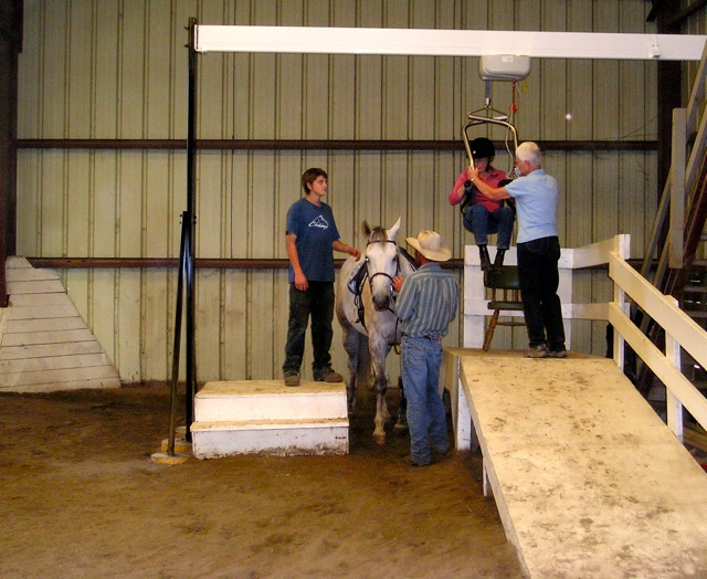 challenged rider being lifted onto a horse