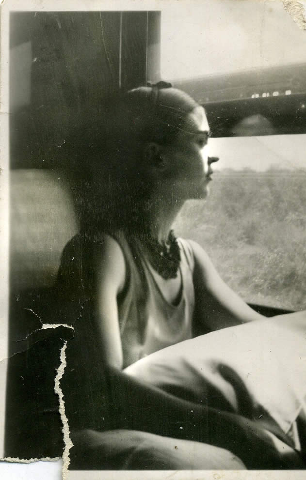 Frida pictured looking out a window (http://www.museofridakahlo.org.mx/esp/1/frida-kahl ())