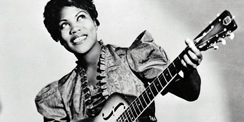 Young Rosetta Tharpe holding a guitar, smiling. (http://bimagazine.org/sister-rosetta-tharpe-bisexu (N/A))